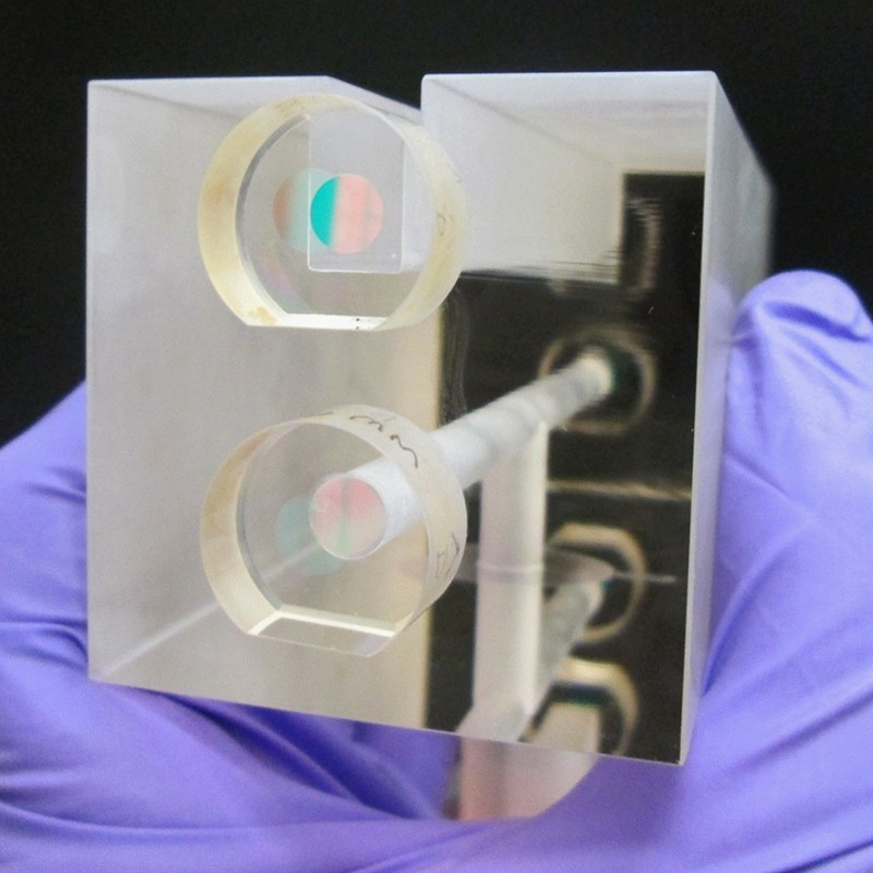 A NIST researcher holds a fixed length optical cavity (FLOC)