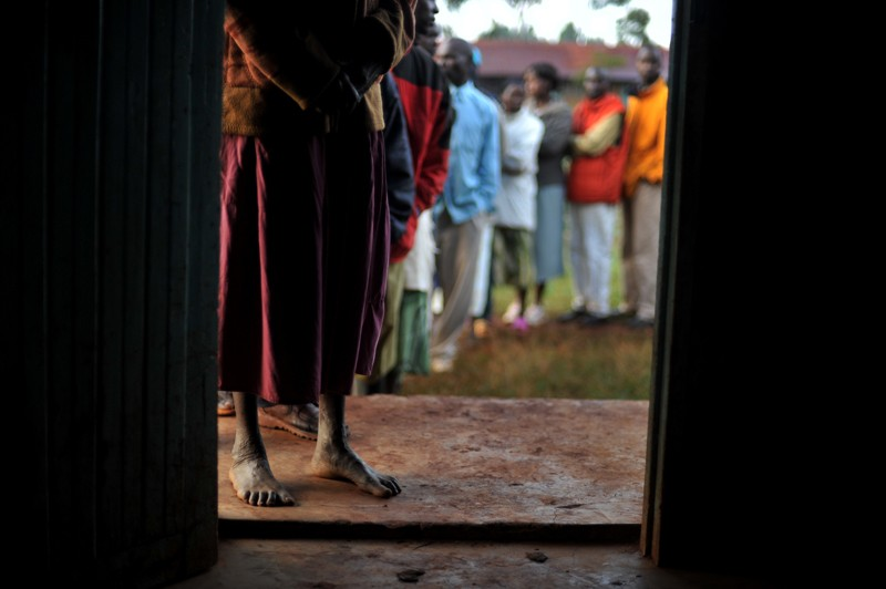 A Kenyan woman with bare feet stands at the front of a line of people waiting to vote