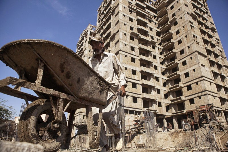 A laborer pushes a wheelbarrow load of concrete on the construction site in Karachi, Pakistan