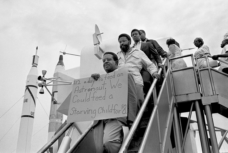 Protesters walk down steps at the Apollo 11 moon launch on 15 July 1969
