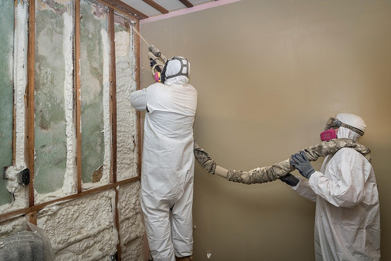 Workers spraying open-cell foam insulation on interior walls ofa home