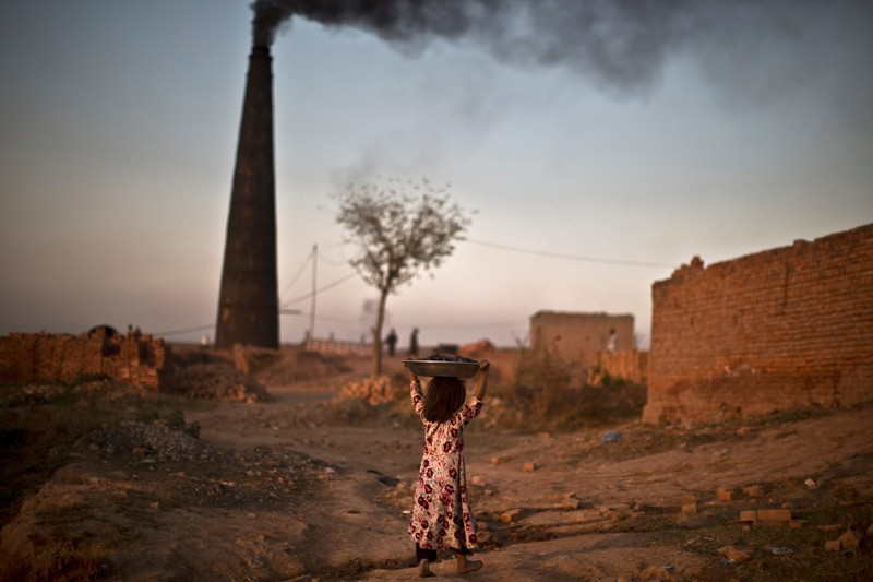 A young girl walks by a smoking chimney carrying a pan of coal on her head, Islamabad, Pakistan.