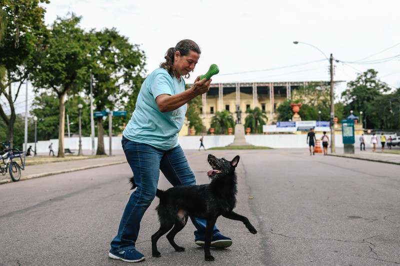 Astronomer Maria Elizabeth Zucolotto plays with her dog, Fumaça, in front of the National Museum in Rio de Janeiro