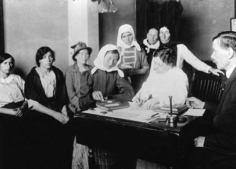 Black and white photo of a woman doing a puzzle at a desk, with other people waiting around her.