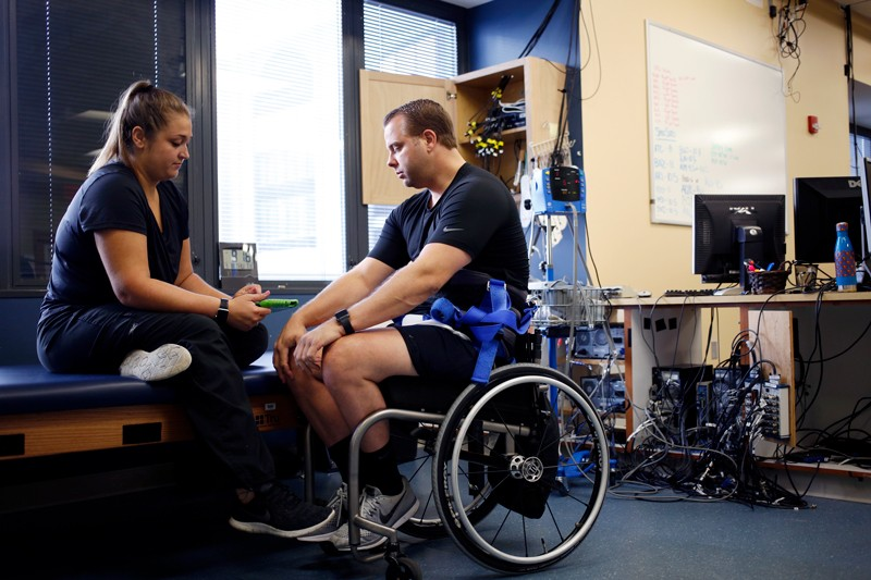 Katie Pfost (Left) controls Rob Summers' spinal stimulator with a tablet before conducting treadmill locomotive training