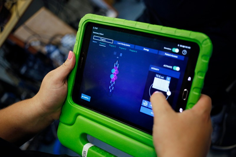 Katie Pfost controls Rob Summers' spinal stimulator with a tablet