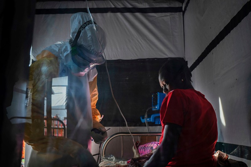 Health workers wearing protective gear check on Ivette Adania, 24, a mother of four whose husband died of Ebola
