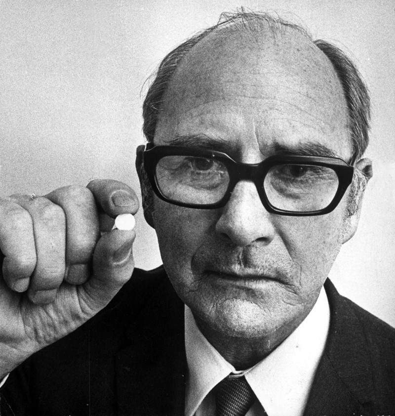 Black and white picture of John Cade in a jacket, tie and glasses, holding a white pill.