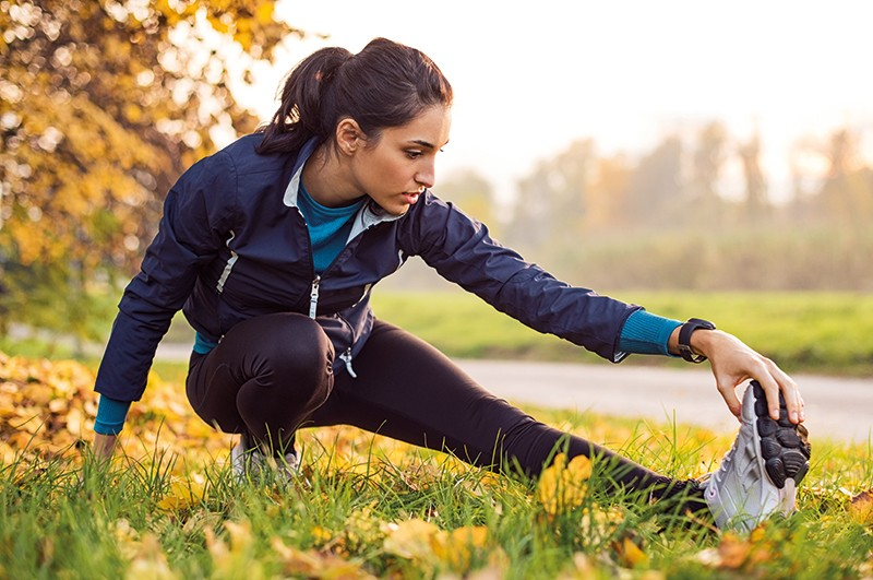 A female runner stretches her leg in a park