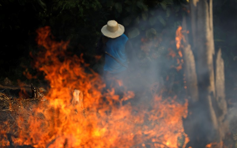 A man works in a burning tract of Amazon jungle as it is being cleared by loggers and farmers in Iranduba, Brazil.