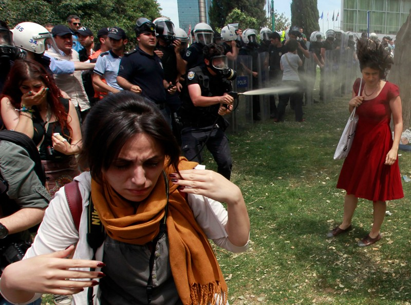 A Turkish riot policeman uses tear gas as people protest against the destruction of trees in a park
