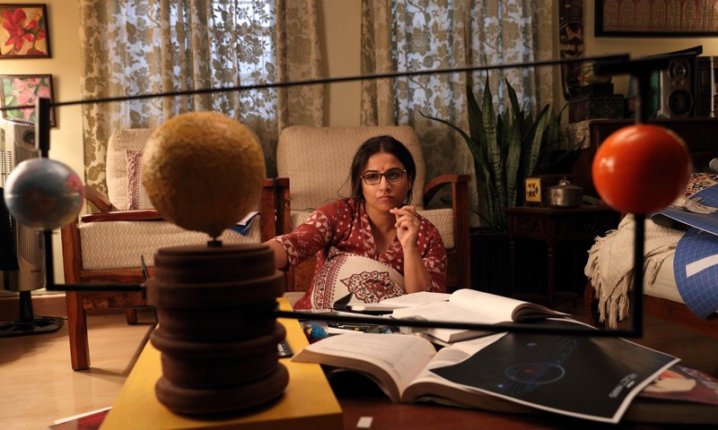 Actress Vidya Balan as project director Tara Shinde - seated at a cluttered desk in front of a solar system model.