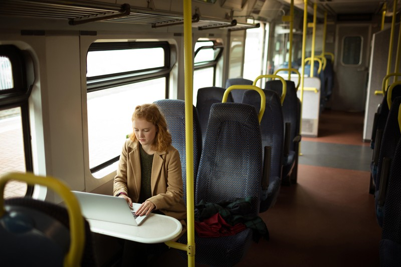 Red-haired young woman using her laptop on a train