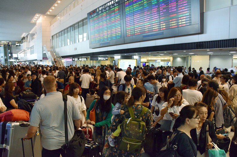 Passengers wait at the arrivals hall of Narita International Airport