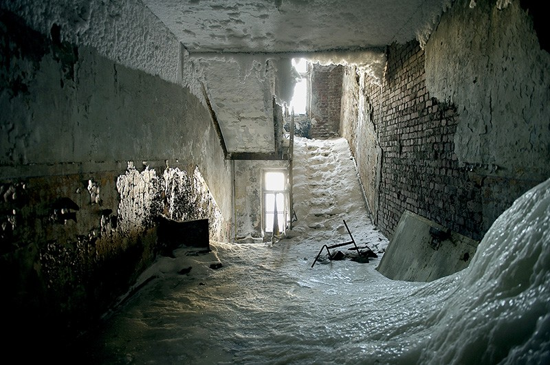 The interior of an abaondoned multi storey building in Norilsk covered in ice