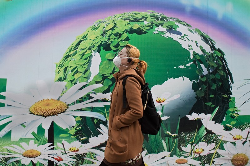 A woman wearing a protective pollution mask walks past a billboard depicting a green globe and flowers in Beijing