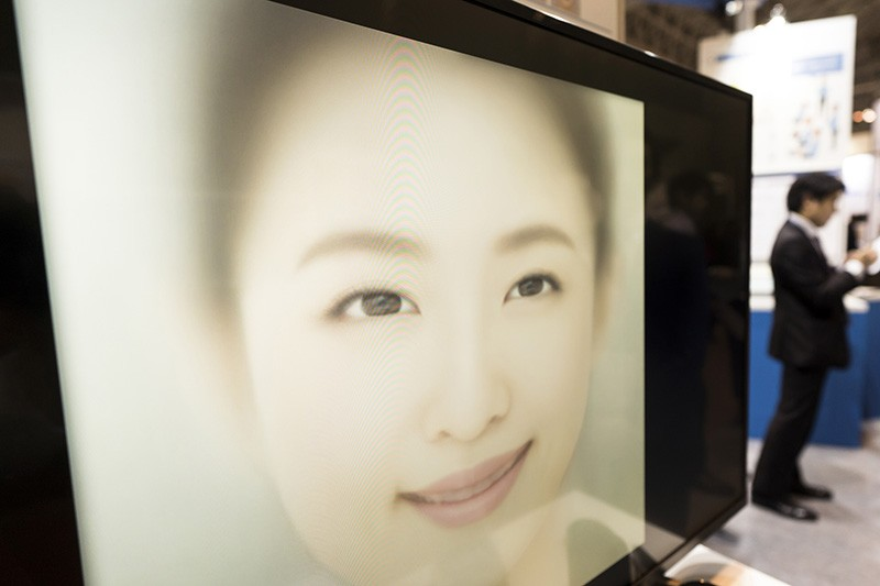A large face on a screen, seen at an angle, with people in the background.