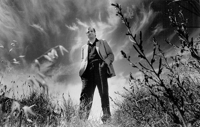 Lo scrittore Douglas Adams in piedi in un campo