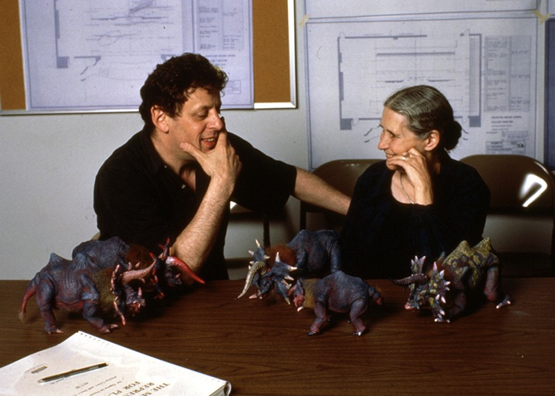 Philip Glass (left) and Doris Lessing (right) in 1988. They are sitting at a table covered in model dinosaurs.