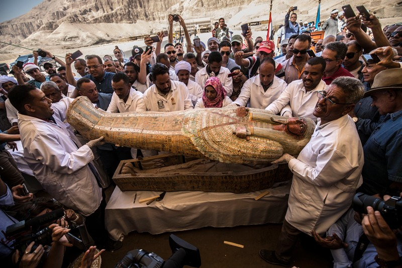 Egyptian archeologists open a wooden coffin belonging to a man in front Hatshepsut Temple at Valley of the Kings in Luxor
